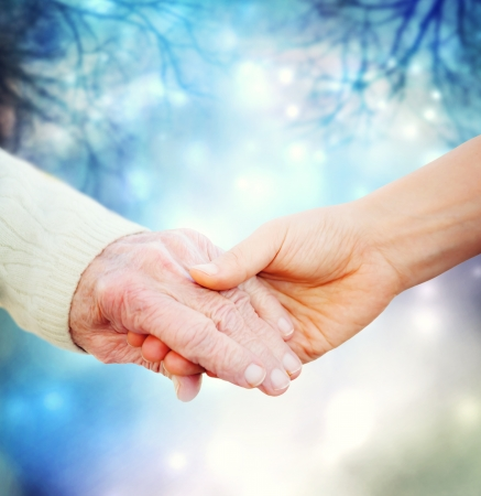 Photo pour Holding hands with an elder on a blue night background - image libre de droit
