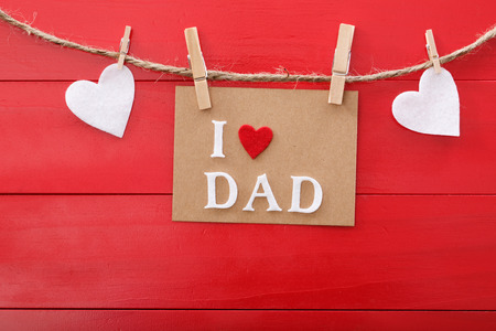 Foto de Fathers day message with felt hearts hanging with clothespins over red wooden board  - Imagen libre de derechos