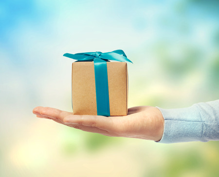 Photo for Small blue ribbon gift box on a hand - Royalty Free Image