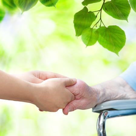 Foto de Elderly woman in wheel chair holding hands with young caretaker - Imagen libre de derechos