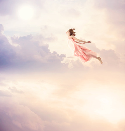 Photo pour Girl in a pink dress flying in the sky. Serenity. - image libre de droit