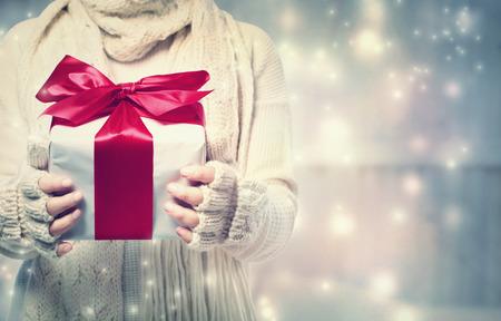 Foto de Woman holding a giftbox with red ribbon in the snowy night - Imagen libre de derechos