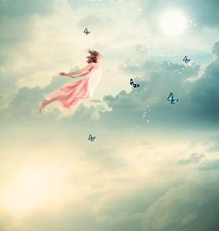 Foto de Blonde Girl Flying with Butterflies at Twilight - Imagen libre de derechos