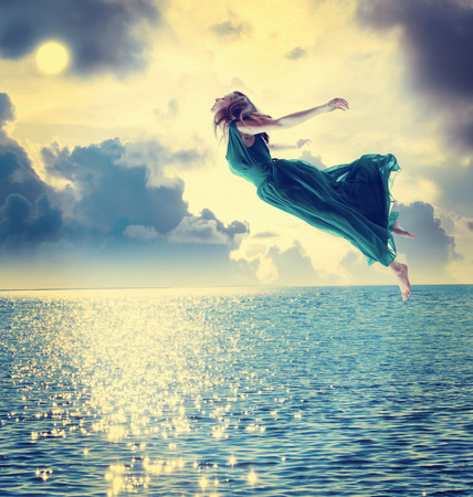 Photo pour Beautiful girl jumping into the blue night sky over the ocean - image libre de droit