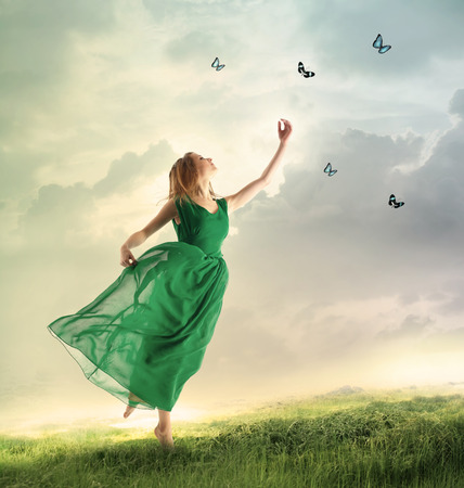 Photo for Beautiful woman in a green dress chasing butterflies on a mountain - Royalty Free Image