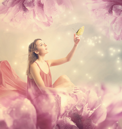 Foto de Beautiful young woman with a small butterfly on peony flower - Imagen libre de derechos