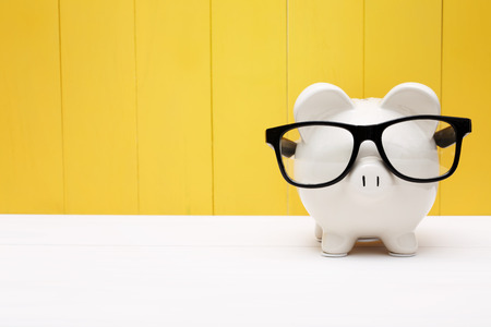Foto de Piggy bank wearing a black glasses over yellow wooden wall - Imagen libre de derechos