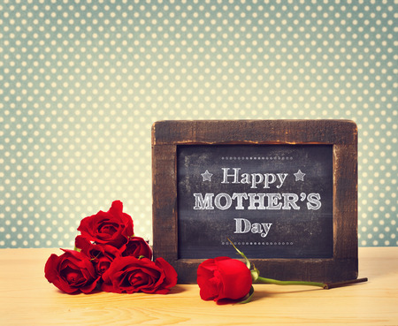Photo for Happy Mothers Day message written on little chalkboard with roses - Royalty Free Image