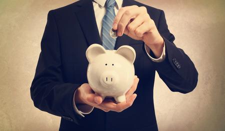 Foto de Young businessman depositing money in piggy bank - Imagen libre de derechos