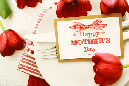 Photo pour Dinner table setting with Mothers day message card and red tulips - image libre de droit
