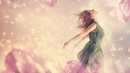 Photo for Beautiful woman in a green dress in a pink peony flower fantasy - Royalty Free Image