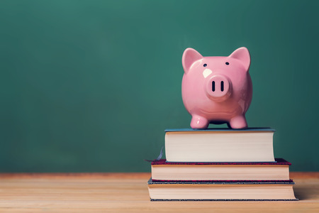 Foto de Pink Piggy bank on top of books with chalkboard in the background - Imagen libre de derechos
