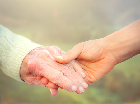 Photo pour Elderly woman holding hands with young caretaker - image libre de droit