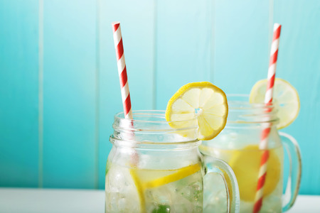 Foto de Homemade lemonade in mason jars with big red striped straws - Imagen libre de derechos
