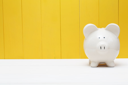Photo pour White piggy bank against a yellow wooden wall - image libre de droit