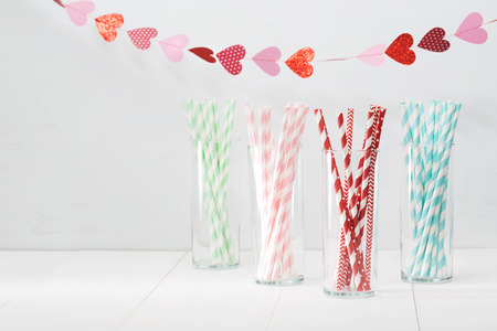 Foto de Colorful paper straws with a decorative garland of hearts symbolic of love to celebrate a party for a festive romantic occasion, with copyspace for your invitation or greeting - Imagen libre de derechos