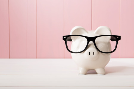 Photo pour Piggy bank with black glasses on pink wooden wall - image libre de droit