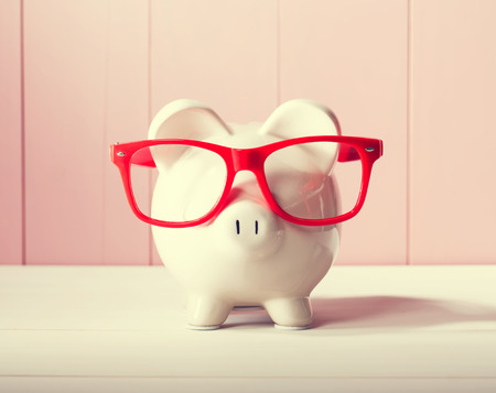 Photo pour Piggy bank with red glasses on pink wooden wall - image libre de droit