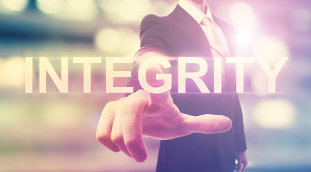 Photo for Businessman pointing at INTEGRITY on blurred city background - Royalty Free Image