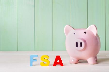 Photo pour Flexible Spending Account FSA concept with pink piggy bank, wood block letters and green background - image libre de droit