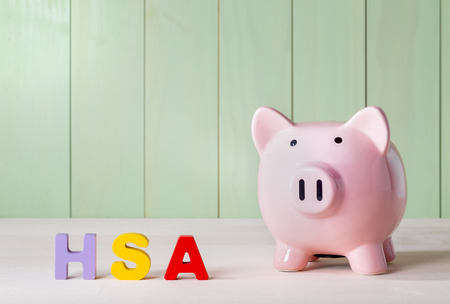 Photo pour Health Savings Account HSA concept with pink piggy bank, wood block letters and green background - image libre de droit