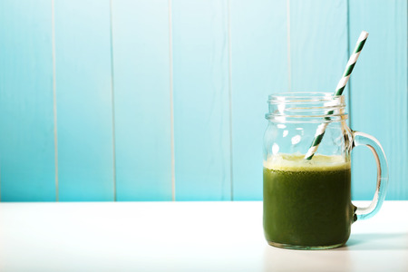 Photo pour Green smoothie in masons jar with paper straw on blue wooden wall - image libre de droit