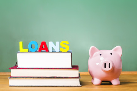 Photo pour Student loan theme with textbooks and piggy bank and green chalkboard background - image libre de droit