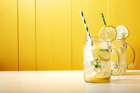 Photo for Homemade lemonade in mason jars with big green paper straw - Royalty Free Image