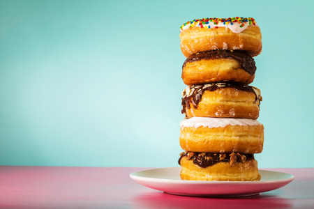 Photo for Stack of assorted donuts on a white plate on pastel blue and pink background - Royalty Free Image