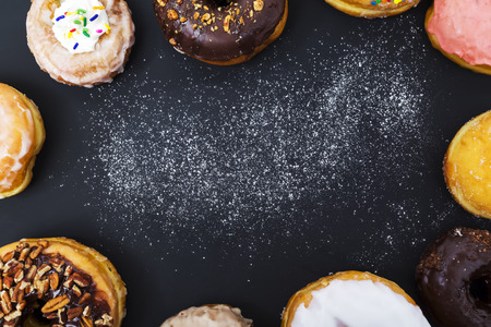 Photo for Assorted donuts with powder flour on black background - Royalty Free Image
