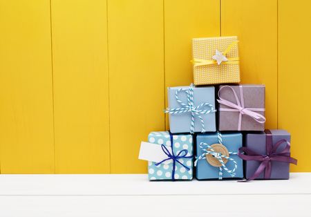 Foto de Stack of little present boxes on yellow wooden wall - Imagen libre de derechos