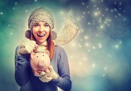 Photo pour Happy young woman depositing money into her pink piggy bank - image libre de droit