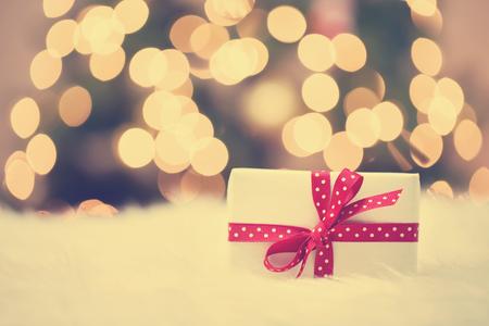 Foto de Christmas gift box on white carpet in frot of tree - Imagen libre de derechos