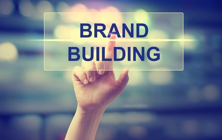 Foto de Hand pressing Brand Building on blurred cityscape background - Imagen libre de derechos