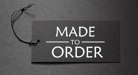 Photo for Made to Order text on a black tag on black paper background - Royalty Free Image