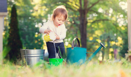 Foto de Happy toddler girl playing with watering cans outside - Imagen libre de derechos