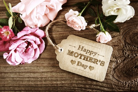 Photo for Mothers Day message with small pink roses on wooden table - Royalty Free Image