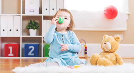 Photo pour Happy toddler girl have tea with her teddy bear - image libre de droit