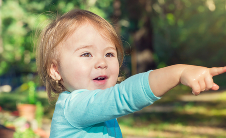 Photo pour Happy toddler girl playing outside on a bright summer day - image libre de droit