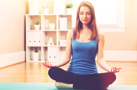 Photo for Young woman practicing meditation at home - Royalty Free Image