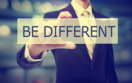 Foto de Business man holding Be Different on blurred abstract background - Imagen libre de derechos