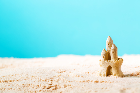 Photo for Summer theme with sand castle on a bright blue background - Royalty Free Image