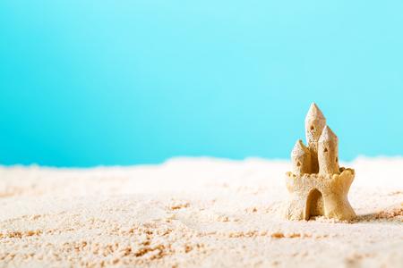 Photo pour Summer theme with sand castle on a bright blue background - image libre de droit