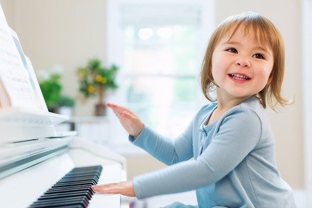 Photo for Happy smiling toddler girl excited to play the piano - Royalty Free Image