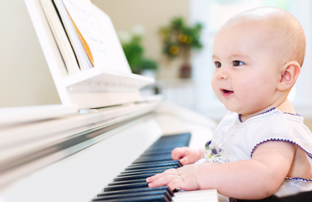 Baby girl playing the piano in her house