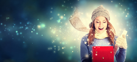 Photo for Happy young woman opening a Christmas present box - Royalty Free Image