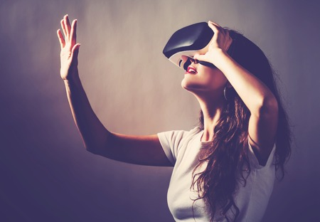 Photo pour Young woman using a virtual reality headset - image libre de droit