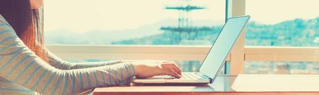 Foto de Woman working on a laptop in brightly lit room - Imagen libre de derechos