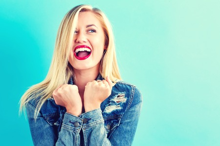 Foto de Happy young woman on a blue background - Imagen libre de derechos