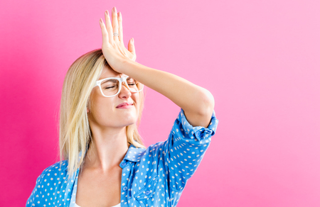 Photo pour Young woman making a mistake on a pink background - image libre de droit
